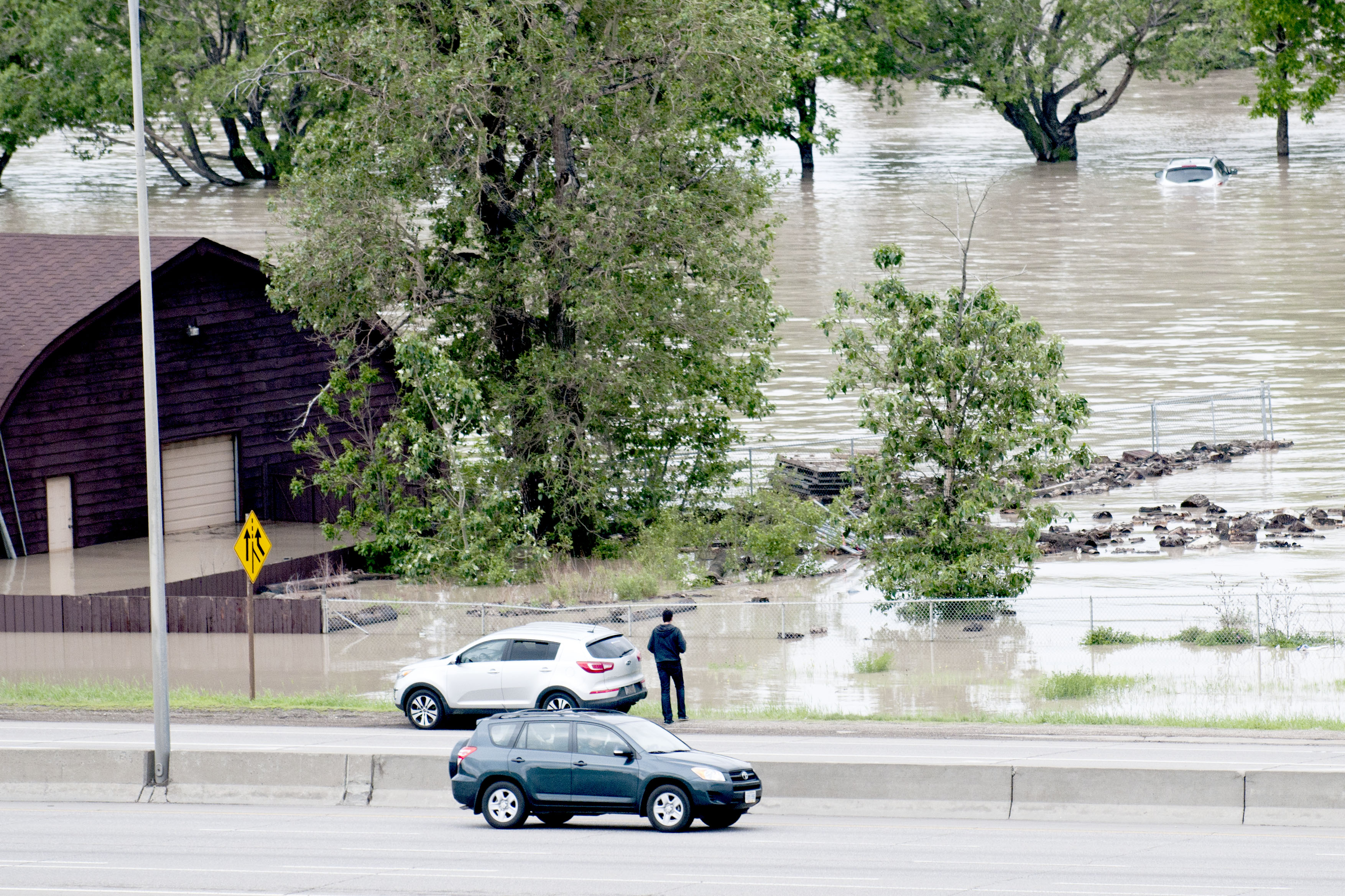 A view from the ridge of Dover overlooking Deerfoot Tr as bystanders pull over to take-in  the devastation, including the underwater Inglewood Golf and Country Club.