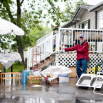 A determined man stands outside of his home in Calgary for a garage sale, which had everything  including a kitchen sink, during the first morning of the flooding,