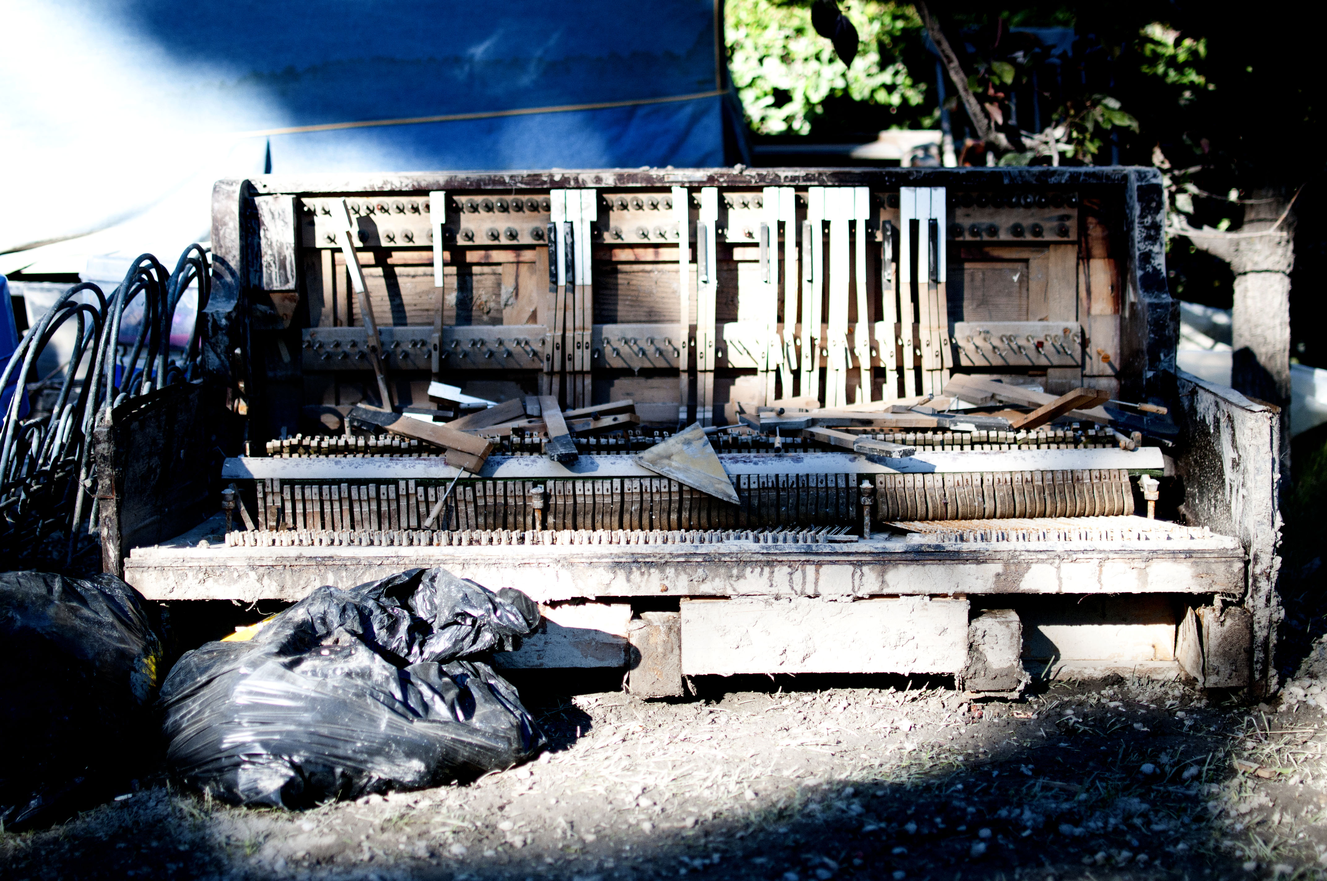 A piano sits destroyed from the heavy waters along the gravel road of Bow Crescent.